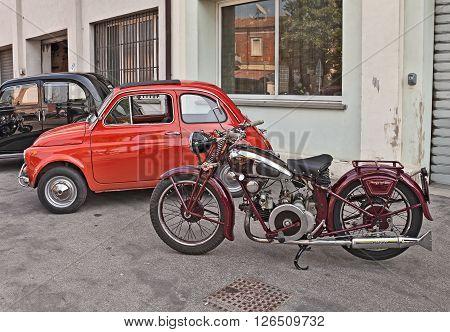 VOLTANA DI LUGO (RA) ITALY - APRIL 10: classic Italian motorbike Moto Guzzi (1939) next to a Fiat 500 in motorcycle rally