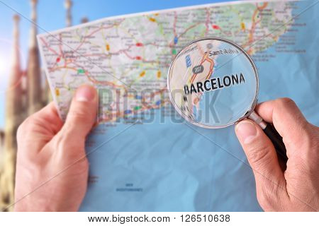 Man Consulting A Map Of Barcelona With A Magnifying Glass