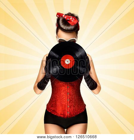 Vintage photo of glamorous pinup girl wearing long gloves and dressed in a red sexy corset hiding behind LP vinyl record on colorful abstract cartoon style background.