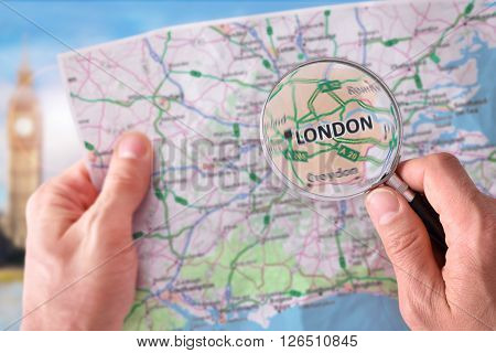 Man Consulting A Map Of London With A Magnifying Glass