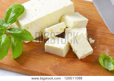 diced feta cheese on wooden cutting board - close up
