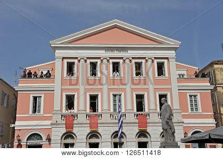 CORFU GREECE - APRIL 18 2009: Ionian Bank building dressed with traditional red banners and people out on the windows watching the lament procession on the morning of Holy Saturday.