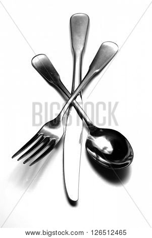 Group of knife fork and spoon stacked on white background