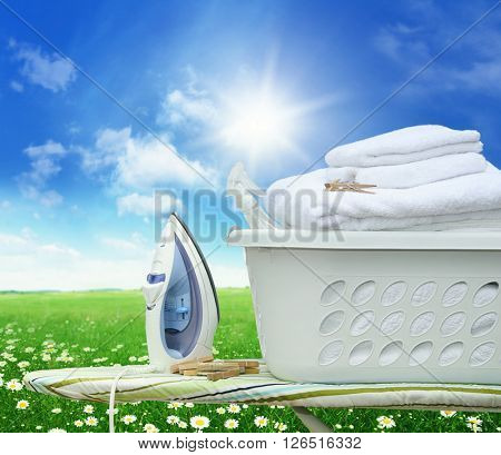 Iron board and iron with laundry basket in field of daisies