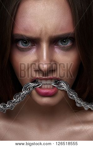 Fashion beauty young Woman with agressive Look and Chain in her Teeth