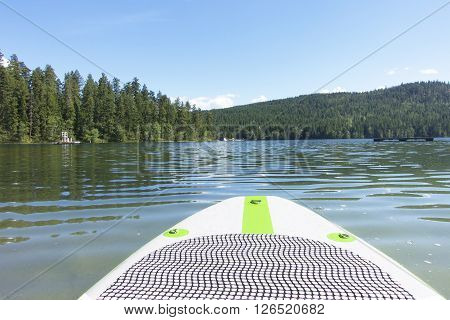 Picture of the front of a paddle board on a lake in the Shuswap area,British Columbia,Canada.