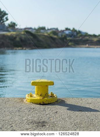 Cleat for mooring boats. Space for text insertion on the right.yellow