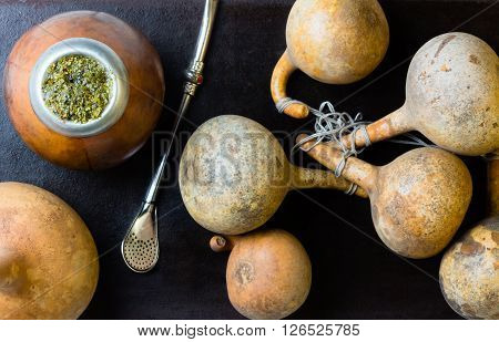 Yerba Herb mate in calabash and calabashes on black background. Top view