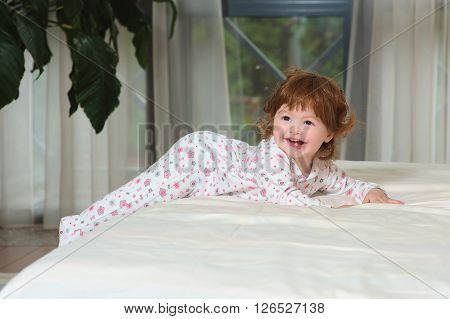 Smiling toddler girl playing in a night clothes on the bed in the bedroom with white linens. Happy curled red-haired baby.