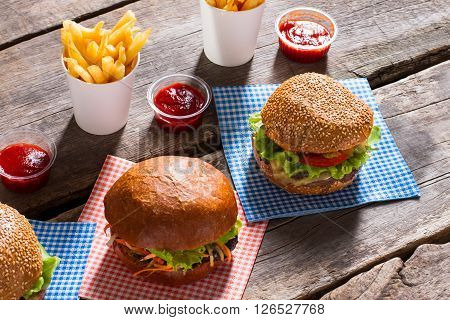 Burgers and fries with sauce. Delicious snack on wooden table. Secret recipe of burgers. The definition of tasty.