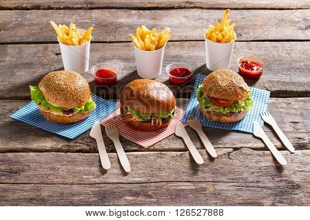Fries with cutlery and burgers. Food with sauce on table. Meal that brings pleasure. Good source of energy.