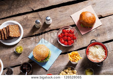 Burgers with tomatoes and bread. Tomatoes and hamburgers on table. Junk food or tasty vegetables. Humble birthday meal.