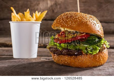Burger on stick and fries. Delicious burger on wooden background. High-calorie dish in cafe. Fresh lettuce and juicy meat.