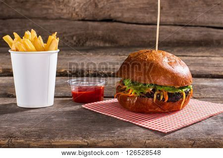 Fries with ketchup and burger. Table with burger on stick. Traditional hamburger in retro diner. Chef's secret recipe.