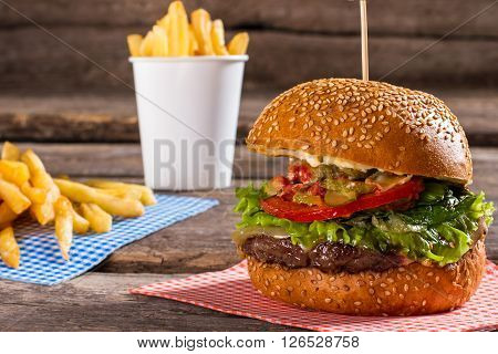 Burger with pile of fries. Beef burger near french fries. Fast food meal on table. Best dish in cafe's menu.