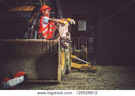 The Man and the Machine. Bulldozer and Excavator Operator Break at Work. Professional Caucasian Construction Machines Operator.