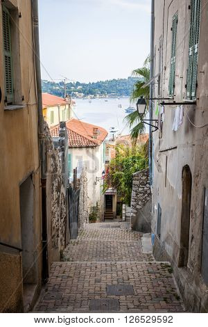 Narrow street with old buildings leading to Mediterranean sea in medieval town Villefranche-sur-Mer on French Riviera, France.