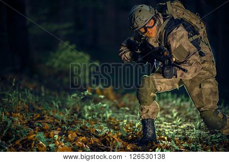 Night Time Special Operation. Running Troop Soldier with Assault Rifle at Night in the Forest.