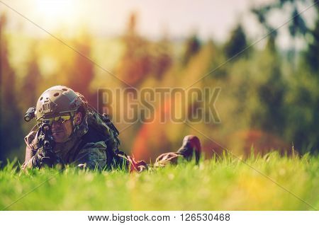 Soldier with Rifle Spotting Enemy While Laying on the Grass Army and Military Concept Photo with Copy Space. military Operation.