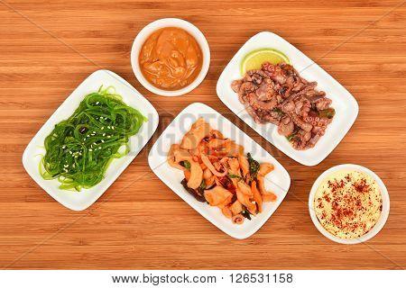 Three Seafood Salads With Sauce On Wood