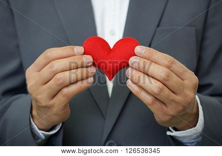 Businessman giving a red heart to a customer on isolated background - customer relationship management