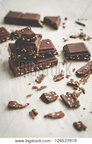 Chocolate bar and pices on wooden table. Selective focus vintage style