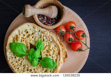 Italian dried bread Friselle on wooden board with tomatoes cherry, basil and peppercorns in wooden pounder. Italian food. Healthy vegetarian food.