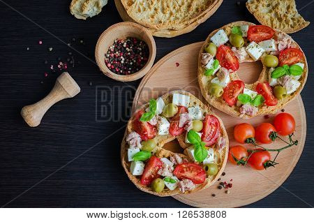 Italian appetizer Friselle. Italian dried bread Friselle on wooden board with tomatoes cherry, olives, tuna, basil and peppercorns. Italian food. A quick and easy snack for party time.