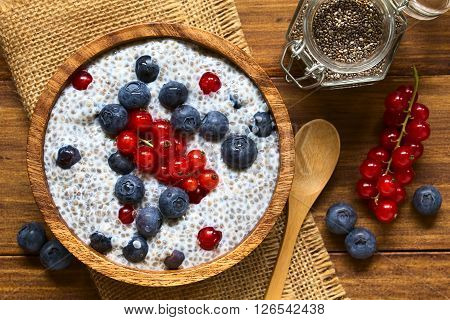Chia (lat. Salvia hispanica) seed pudding with blueberries and redcurrants in wooden bowl photographed overhead on wood with natural light (Selective Focus Focus on the top of the pudding)
