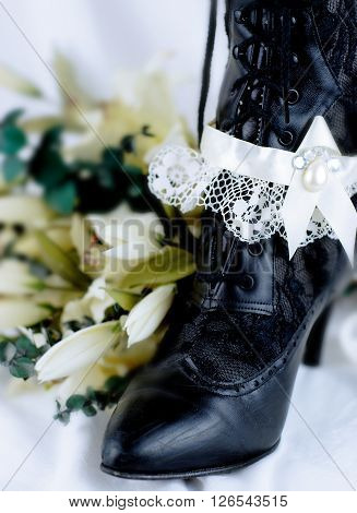 A pair of vintage and worn black, woman's wedding boot. An ivory colored satin and lace garter hangs on one of the boots which are in front of soft, white draped cotton