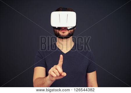 Beard man in black t-shirt is touching something with his right hand using virtual reality glasses, on black background