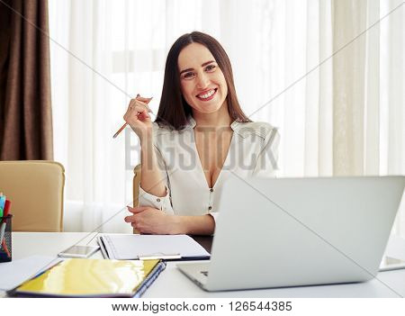 Young smiling woman holding a pen in her right hand in white modern office