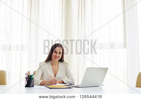 Smiling woman writing some data in a pad and looking directly in the white modern office