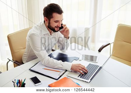 Man working on the laptop and calling someone on the phone in the modern white office, view from above