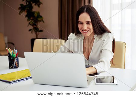 Young smiling brunette working on her notebook  in modern white office