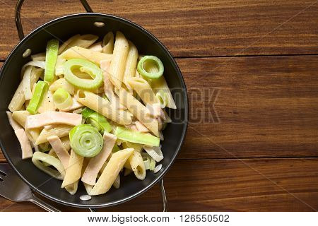 Pasta dish with ham and leek in cream sauce served in bowl photographed overhead on dark wood with natural light (Selective Focus Focus on the top of the dish)