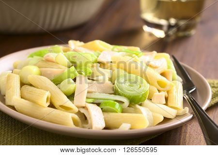 Pasta dish with ham and leek in cream sauce served on plate photographed overhead on dark wood with natural light (Selective Focus Focus one third into the dish)