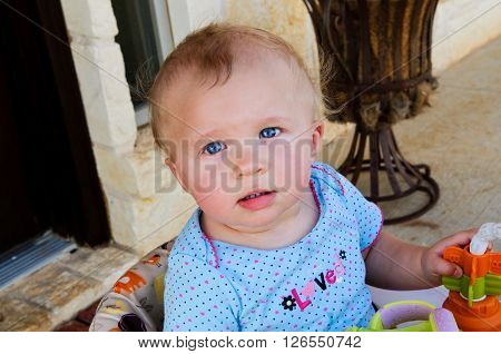 Close-up of sweet baby girl sitting in seat looking at camera