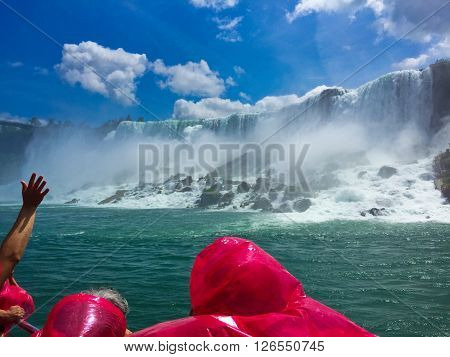 Beautiful Niagara Falls from on a boat with tourist wearing rain jackets.