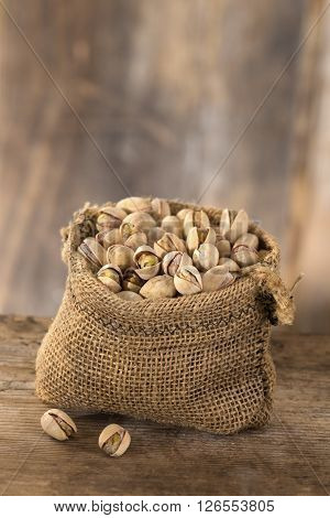 roasted salty pistachios nuts in sack bag, above view