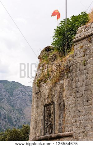 Relief on the Kotor's old town outer defence wall of the south bastion with the Montenegrin flag