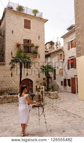KOTOR MONTENEGRO - AUGUST 30 2009: Young female artist painting a picture of the pharmacy house in the old town
