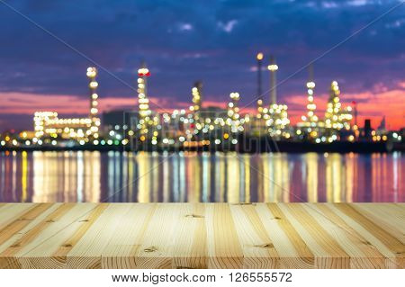 Bokeh of oil refinery at twilight with wood table.