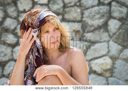 Portrait Of A Beautiful Middle Age Caucasian Woman With Brown Scarf Tied On A Head Against The Stone