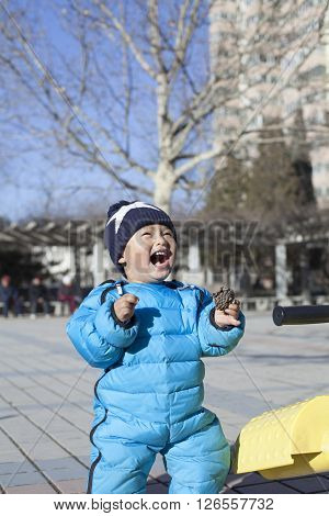 Cute Chinese baby boy playing seesaw outdoors shot in Beijing China
