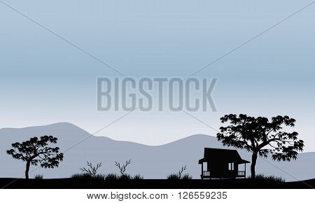 Silhouette of hut with trees and mountain backgrounds