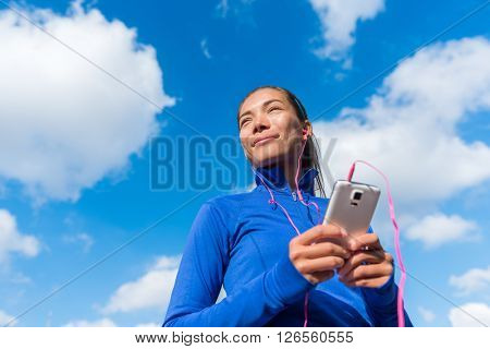 Running lifestyle woman listening to fitness music playlist on smart phone wearing earphones or in ear headphones. Female going for run training in under the blue sky. Runner girl outdoor.