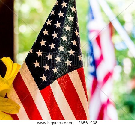 Close-up shot of an American flag beside some yellow flowers with another American flag in the background.