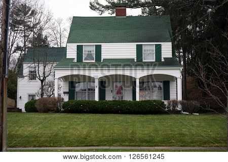 HARBOR SPRINGS, MICHIGAN / UNITED STATES - DECEMBER 23, 2015: A white home with a green roof and a front porch, decorated for the Christmas Holiday, on Traverse Street in Harbor Springs.