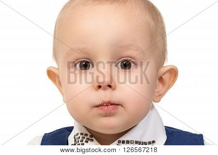 Close-up portrait of a little boy a lips and face full of of crumbs isolated on white background